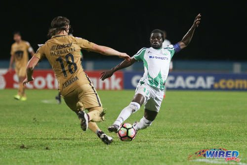 Photo: W Connection captain Hughtun Hector (right) tries to elude Pumas UNAM opponent Jose Garcia during CONCACAF Champions League action in Couva on 3 August 2016. Pumas won 4-2. (Courtesy Chevaughn Christopher/Wired868)