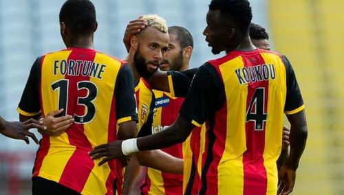 Photo: Lens midfielder John Bostock (centre) is congratulated by his teammates.