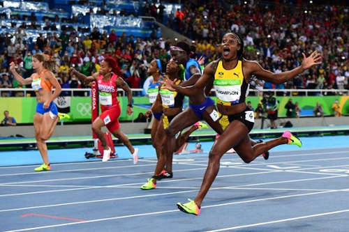 Photo: Jamaica's Elaine Thompson celebrates winning the Women's 100m Final at the Rio 2016 Olympic Games in Rio de Janeiro on 13 August 2016.  Trinidad and Tobago's Michelle-Lee Ahye is second from left. (Copyright AFP 2016/Franck Fife)
