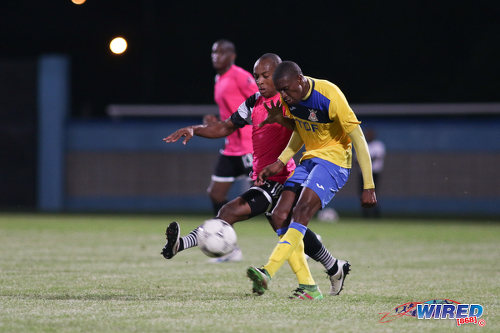Photo: Defence Force playmaker Hashim Arcia (right) has his effort blocked by Central FC captain Leston Paul during the Digicel Charity Shield on 10 September 2016. Central won 3-1 from kicks from the penalty mark after a 2-2 regulation time draw. (Courtesy Chevaughn Christopher/Wired868)