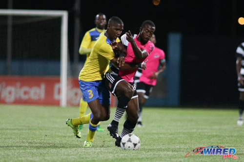 Photo: Central FC attacker Marcus Joseph (right) tries to hold off Defence Force defender Jamali Garcia during the Digicel Charity Shield on 10 September 2016. Garcia and Joseph are both capped by Trinidad and Tobago National Senior Team coach Stephen Hart. (Courtesy Chevaughn Christopher/Wired868)