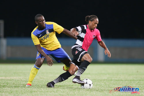 Photo: Defence Force striker Devorn Jorsling (left) chases Central FC midfielder Nathaniel Garcia during the Digicel Charity Shield on 10 September 2016. (Courtesy Chevaughn Christopher/Wired868)
