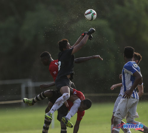 Photo: St Mary's College goalkeeper Jordan Bidaisee (centre) punches the ball away during SSFL Premier Division action against Pleasantville Secondary on 10 September at Serpentine Road. (Courtesy Sean Morrison/Wired868)