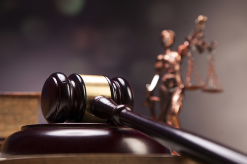 Photo: A court gavel and miniature statute of Lady Justice.