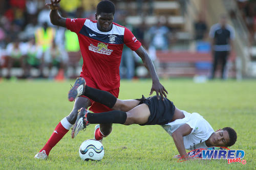 Photo: Fyzabad midfield bouncer Kaylon Padilla (left) bowls over St Anthony's College captain Jules Lee during SSFL Premier Division action on 24 September 2016 at Fyzabad. (Courtesy Chevaughn Christopher/Wired868)