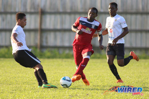 Photo: Fyzabad Secondary Sharkeel Louison (centre) passes the ball during SSFL Premier Division action against St Anthony's College on 24 September 2016 at Fyzabad. (Courtesy Chevaughn Christopher/Wired868)