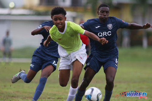 Photo: St Augustine player Tajh Devenish (centre) tries to hold off QRC's Miguel Williams during SSFL Premier Division action at the QRC grounds on 8 September 2016. (Courtesy Chevaughn Christopher/Wired868)