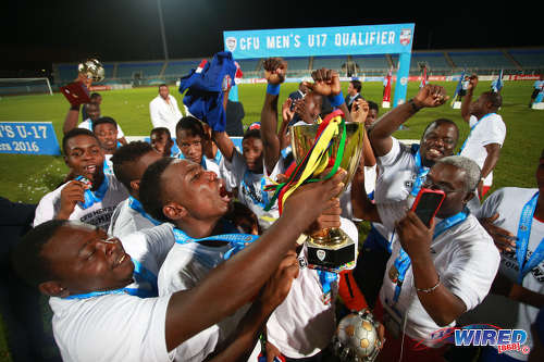Photo: The Haiti National Under-17 Team celebrates with the Caribbean Cup trophy after trouncing Cuba 5-0 in the CFU final on 25 September 2016 at the Ato Boldon Stadium in Couva. (Courtesy Allan V Crane/Wired868)