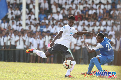 Photo: Naparima College forward Isaiah Lee (left) takes his aim while Presentation College (San Fernando) midfielder Kori Cupid looks on during SSFL Premier Division action at Lewis Street, San Fernando on 28 September 2016. Lee scored one and set up another as Naparima won 2-0. (Courtesy Allan V Crane/Wired868)