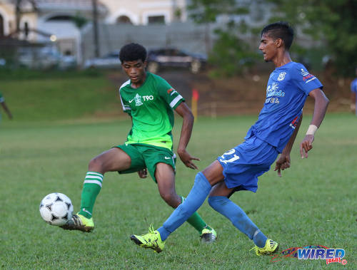 Photo: Naparima College midfielder Justin Sadoo (right) passes the ball past a Trinity College Moka opponent during SSFL Premier Division action on 21 September 2016 at Moka. (Courtesy Sean Morrison/Wired868)