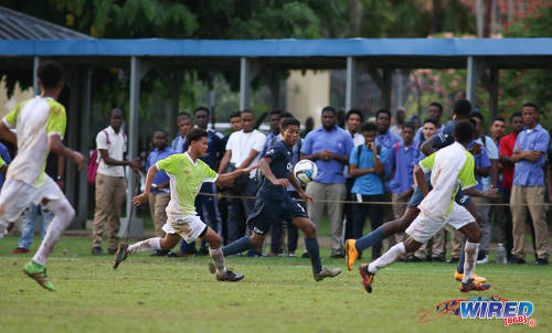 Photo: QRC midfielder Keyshawn Villafana (centre) runs at St Augustine opponents during SSFL Premier Division action at the QRC grounds on 8 September 2016. (Courtesy Chevaughn Christopher/Wired868)