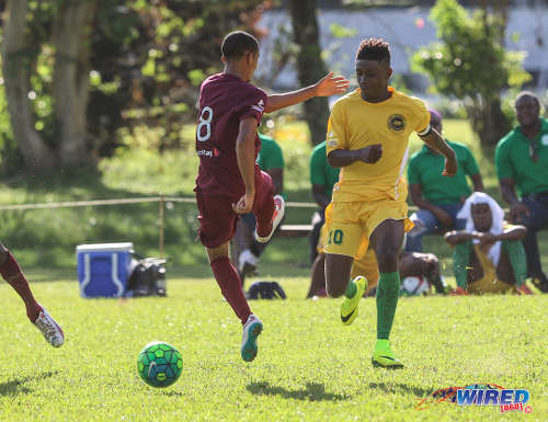 Photo: Signal Hill Secondary captain Akil Frank (right) slips the ball past East Mucurapo player Joshua Constantine during SSFL Premier Division action at Moka on 14 September 2016. (Courtesy Sean Morrison/Wired868)
