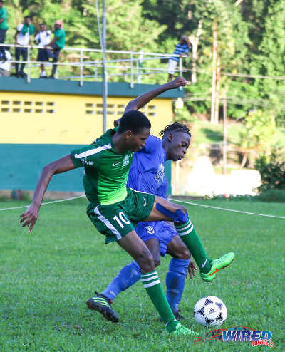 Photo: Trinity College Moka forward Isaiah McLean (left) tries to escape from Naparima College left back Khris Stroud during SSFL Premier Division action on 21 September 2016 at Moka. (Courtesy Sean Morrison/Wired868)