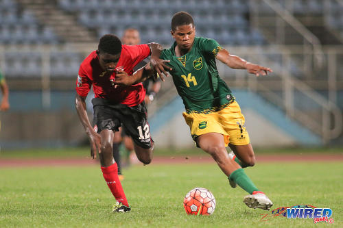 Photo: Trinidad and Tobago right back Jerrin Jackie (left) tries to keep up with Jamaica attacker Nicque Daley during Caribbean Football Union (CFU) Under-17 action on 20 September 2016 at the Ato Boldon Stadium in Couva. (Courtesy Chevaughn Christopher/Wired868)