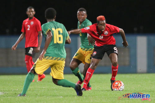Photo: Trinidad and Tobago National Under-17 Team midfielder Jodel Brown (right) holds off Jamaica forward Raewin Senior (second from right) during Caribbean Football Union (CFU) action on 20 September 2016 at the Ato Boldon Stadium in Couva. (Courtesy Chevaughn Christopher/Wired868)