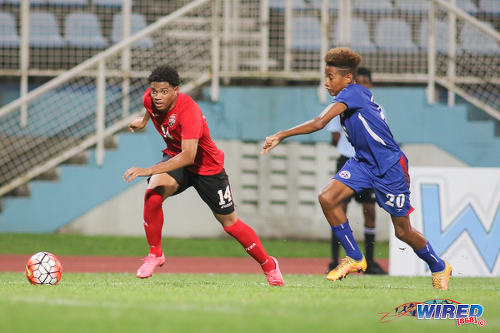 Photo: Trinidad and Tobago National Under-17 midfielder Kishon Hackshaw (left) races away from Bermuda full back Richard Jones during 2017 World Cup qualifying action at the Ato Boldon Stadium on 18 September 2016. (Courtesy Chevaughn Christopher/Wired868)