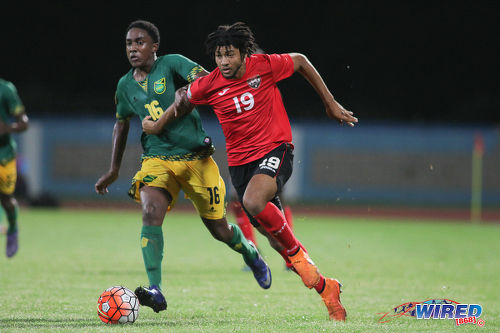 Photo: Trinidad and Tobago forward Nion Lammy (right) motors past Jamaica defender Blake White during Caribbean Football Union (CFU) action on 20 September 2016 at the Ato Boldon Stadium in Couva. (Courtesy Chevaughn Christopher/Wired868)