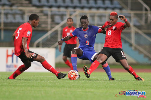 Photo: Haiti forward Nael Elysee (centre) tries to escape from the attentions of Trinidad and Tobago midfielder Jodel Brown (right) and defender Jesse Williams during 2017 World Cup qualifying action in Couva on 17 September 2016. Elysee scored the opener as Haiti won 2-0. (Courtesy Chevaughn Christopher/Wired868)