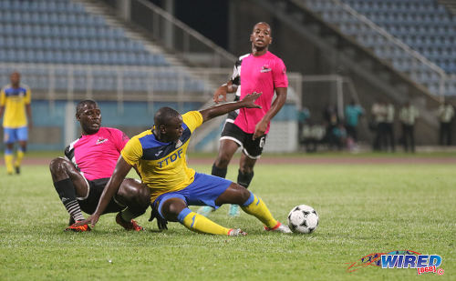 Photo: Defence Force striker Devorn Jorsling (centre) keeps his eye on the ball while Central FC players Keion Goodridge (left) and Leston Paul look on during Pro League action at the Ato Boldon Stadium in Couva on 14 October 2016. (Courtesy Sean Morrison/Wired868)