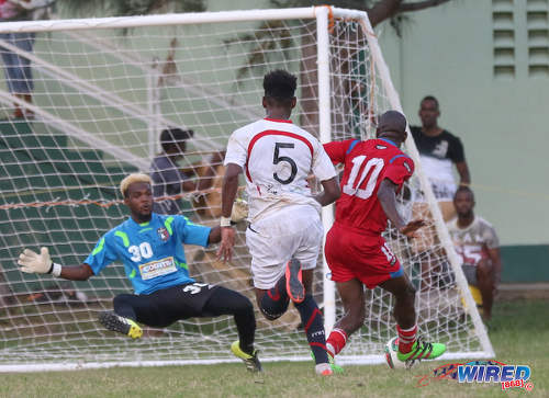 Photo: St Ann's Rangers forward Devon Modeste (right) shoots wide under pressure by Morvant Caledonia United goalkeeper Stephon Seepersad (left) and defender Seon Thomas during Pro League action at the Barataria Recreation Ground on 9 October 2016. (Courtesy Sean Morrison/Wired868)