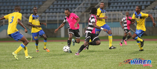 Photo: Central FC midfielder Leston Paul (centre) tries to find through a packed Defence Force rearguard during Pro League action at the Ato Boldon Stadium in Couva on 14 October 2016. (Courtesy Sean Morrison/Wired868)