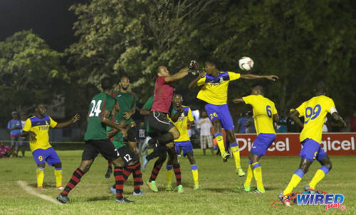 Photo: San Juan Jabloteh goalkeeper Shemel Louison (centre) punches away the ball under pressure from Defence Force left back Justin Garcia (third from right) during Pro League action at the Barataria Recreation Ground on 9 October 2016. (Courtesy Sean Morrison/Wired868)