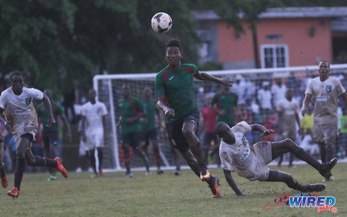 Photo: San Juan Jabloteh striker Willis Plaza (centre) leaves fallen Morvant Caledonia United defender Taje Commissiong for dead during Pro League action at the Morvant Recreation Ground on 16 October 2016. (Courtesy Sean Morrison/Wired868)
