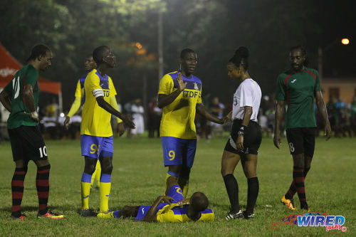 Photo: Defence Force striker Devorn Jorsling (centre) pleads his case to referee Crystal Sobers while teammate Jemel Sebro (lying) awaits the verdict and team captain Jerwyn Balthazar (second from left) pays close attention during Pro League action at the Barataria Recreation Ground on 9 October 2016. Looking on are San Juan Jabloteh players Tyrone Charles (far left) and Keyon Edwards. (Courtesy Sean Morrison/Wired868)