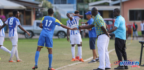 Photo: Shiva Boys Hindu College coach Hayden Ryan (second from right) hands a water bottle to winger Ronaldo Edwards during SSFL Premier Division action against St Mary's College at Lachoo Road on 19 October 2016. (Courtesy Sean Morrison/Wired868)