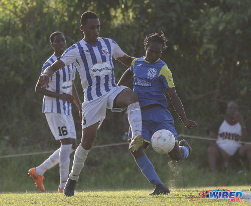 "Photo: St Mary's College defender Joshua Joseph (left) tries in vain to stop an effort by Shiva Boys Hindu College attacker Tyrell ""Sexyman"" Baptiste during SSFL Premier Division action at Lachoo Road on 19 October 2016. (Courtesy Sean Morrison/Wired868)"