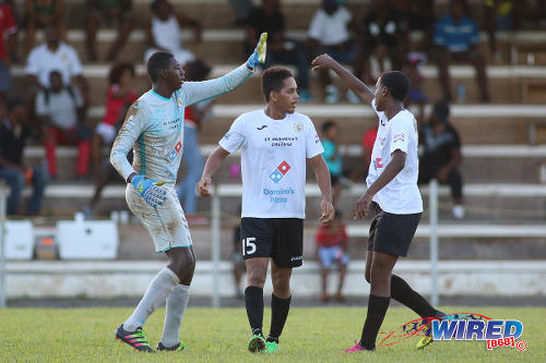Photo: St Anthony's College defender Nicholas Moyou (centre) and goalkeeper Jabari Brice (left) take a breather during SSFL Premier Division action against Fyzabad on 24 September 2016. (Courtesy Chevaughn Christopher/Wired868)