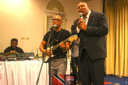 Photo: Trinidad and Tobago Football Association (TTFA) president David John-Williams (right) performs a duet with former Calypso Monarch, Cro Cro, at the launch of the National Elite Youth Development Program at the Trinidad Hilton on 14 October 2016. (Copyright TTFA Media)