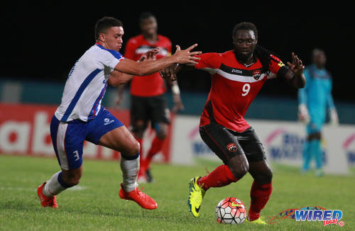 Photo: Trinidad and Tobago captain Kenwyne Jones (right) holds off Dominican Republic defender César Garcia during 2017 Caribbean Cup qualifying action at the Ato Boldon Stadium in Couva on 5 October 2016. (Courtesy Nicholas Bhajan/Wired868)