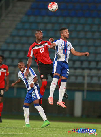 Photo: Trinidad and Tobago defensive midfielder Kevan George (centre) challenges Dominican Republic midfielder Rafael Flores (right) in the air during 2017 Caribbean Cup qualifying action at the Ato Boldon Stadium in Couva on 5 October 2016. (Courtesy Nicholas Bhajan/Wired868)