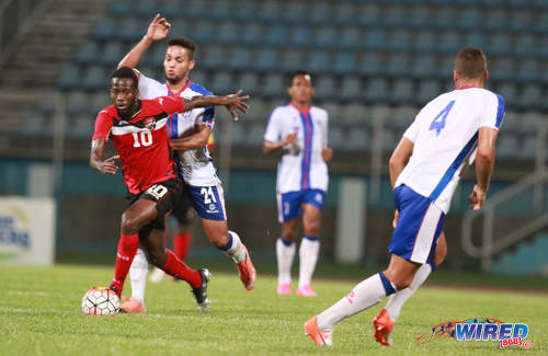 Photo: Trinidad and Tobago attacker Kevin Molino (left) tries to escape from Dominican Republic midfielder Rafael Flores during 2017 Caribbean Cup qualifying action at the Ato Boldon Stadium in Couva on 5 October 2016. (Courtesy Nicholas Bhajan/Wired868)