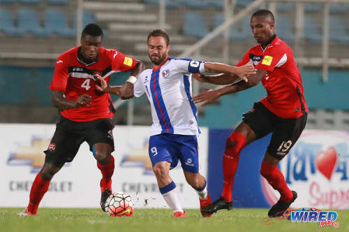 Photo: Dominican Republic captain Jonathan Faña (centre) tries to hold off Trinidad and Tobago players Sheldon Bateau (left) and Kevan George during 2017 Caribbean Cup qualifying action at the Ato Boldon Stadium in Couva on 5 October 2016. (Courtesy Nicholas Bhajan/Wired868)