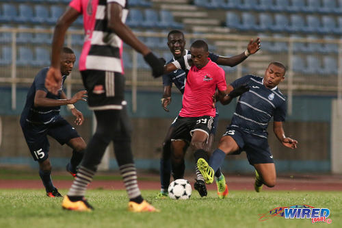 "Photo: Central FC attacker Marcus ""Lobo"" Joseph (centre) is harassed by Police FC midfielders Kenaz Williams (right) and Kurdell Brathwaite (background) during Pro League action at the Ato Boldon Stadium on 4 November 2016. (Courtesy Chevaughn Christopher/Wired868)"