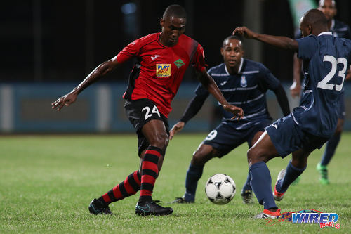 Photo: San Juan Jabloteh defender Adrian Reid (left) tries to force his way past two opponents during Pro League action against Police FC at the Ato Boldon Stadium on 1 November 2016. Jabloteh won 3-2. (Courtesy Chevaughn Christopher/Wired868)