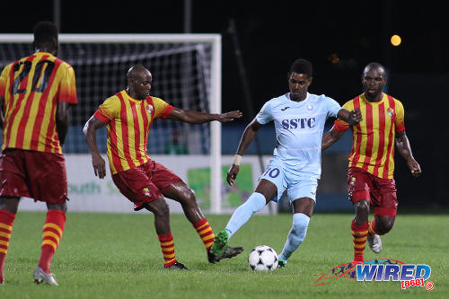 Photo: Police FC attacker Kareem Freitas (centre) tries to keep the ball from Point Fortin Civic midfielder Nickcolson Thomas (second from left) during First Citizens Cup action at the Ato Boldon Stadium in Couva on 14 November 2016. (Courtesy Chevaughn Christopher/Wired868)