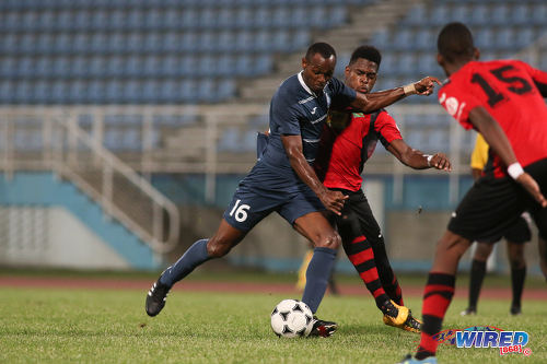 Photo: Police FC striker Keion Wilson (left) prepares to drive home despite the attentions of San Juan Jabloteh defender Josiah Trimmingham (centre) during Pro League at the Ato Boldon Stadium on 1 November 2016. Jabloteh won 3-2. (Courtesy Chevaughn Christopher/Wired868)