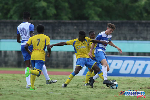 Photo: Presentation College (San Fernando) forward James Alex Lee Yaw (far right) tries to escape from a Shiva Boys Hindu College opponent during the South Zone Intercol final at the Mannie Ramjohn Stadium on 18 November 2016. Presentation won on kicks from the penalty mark. (Courtesy Chevaughn Christopher/Wired868)