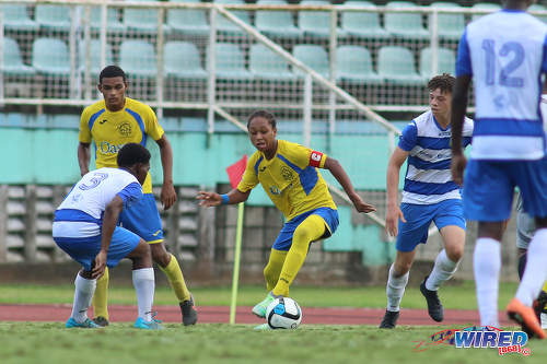 Photo: Shiva Boys Hindu College playmaker and captain Judah Garcia (centre) tries to create space for himself while Presentation College (San Fernando) forward James Alex Lee Yaw (second from right) looks on during the South Zone Intercol final at the Mannie Ramjohn Stadium on 18 November 2016. (Courtesy Chevaughn Christopher/Wired868)