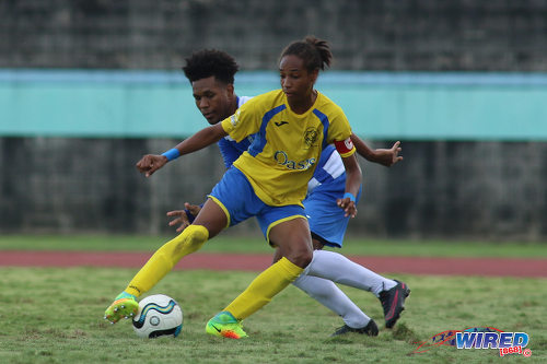 "Photo: Shiva Boys Hindu College maestro Tyrel ""Pappy"" Emmanuel (right) tries to shake off Presentation College (San Fernando) midfielder Terrell Williams during the South Zone Intercol final at the Mannie Ramjohn Stadium on 18 November 2016. (Courtesy Chevaughn Christopher/Wired868)"