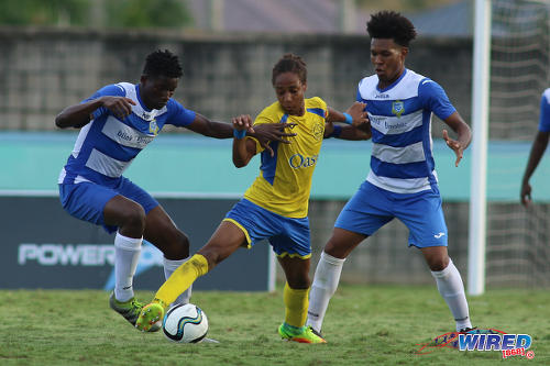 "Photo: Shiva Boys Hindu College maestro Tyrel ""Pappy"" Emmanuel (centre) tries to hold off Presentation College (San Fernando) midfielders Kareem Riley (left) and Terrell Williams during the South Zone Intercol final at the Mannie Ramjohn Stadium on 18 November 2016. (Courtesy Chevaughn Christopher/Wired868)"