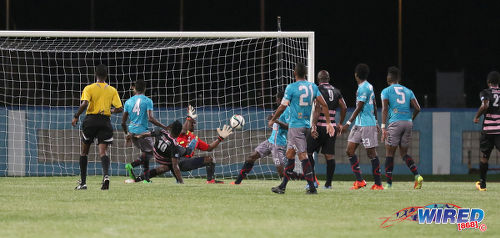 Photo: Ma Pau Stars striker Jerrel Britto (centre) squeezes his shot past Morvant Morvant Caledonia United goalkeeper Marvin Phillip for the decisive goal during Pro League at the Ato Boldon Stadium in Couva on 22 November 2016. (Courtesy Sean Morrison/Wired868)