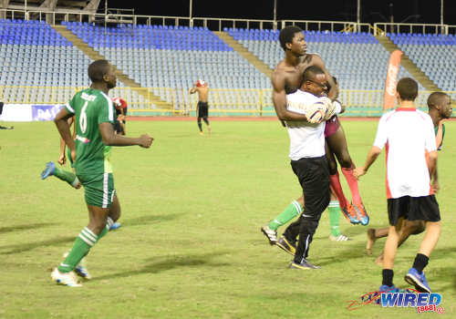 Photo: Trinity College (Moka) goalkeeper Caleb Moore (second from right) is lifted bodily by a member of his coaching staff after helping his school to victory over St Anthony's College in the North Zone Intercol final at the Hasely Crawford Stadium on 25 November 2016. (Courtesy Wired868)