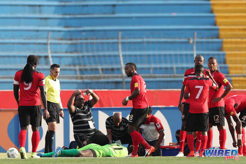 Photo: Trinidad and Tobago National Senior Team medic Dr Terence Babwah (centre) signals for a change while goalkeeper Jan-Michael Williams lays unconscious during 2018 World Cup qualifying action against Honduras in San Pedro Sula on 15 November 2016. (Courtesy Allan V Crane/Wired868)