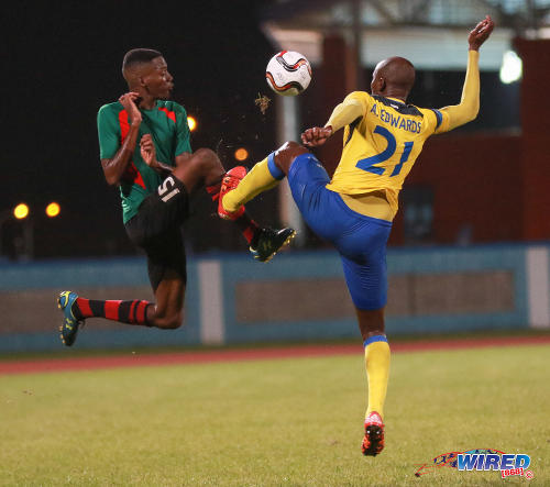 Photo: San Juan Jabloteh defender Jerome Isaiah McIntyre (left) finds himself on the end of a crunching tackle from Defence Force left back Akile Edwards during Pro League action at the Ato Boldon Stadium on 18 September 2016. (Courtesy Sean Morrison/Wired868)