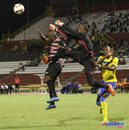 Photo: Defence Force goalkeeper Andre Marchan (centre) punches the ball away from Ma Pau Stars forward Jason Scotland (left) during the First Citizens Bank Cup final at the Hasely Crawford Stadium on 2 December 2016. (Courtesy Sean Morrison/Wired868)