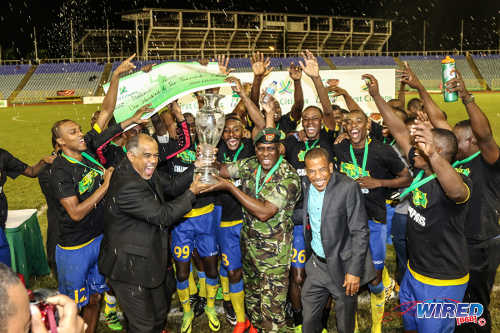 Photo: Defence Force players and staff celebrate with Pro League CEO Dexter Skeene (centre) after beating Ma Pau Stars to the First Citizens Bank Cup title at the Hasely Crawford Stadium on 2 December 2016. (Courtesy Sean Morrison/Wired868)